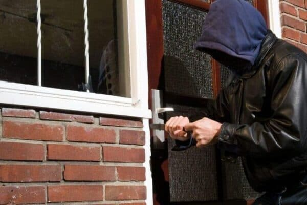 security products - a man attempting to break into a house to commit burglary